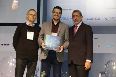O diretor do SAAE, Alysson Diego, recebendo exemplar do livro das mãos de dirigentes da ASSEMAE, no congresso da entidade, em Campinas